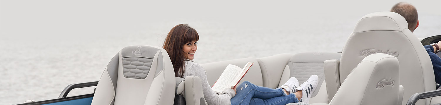 Beautiful woman reading a book on a Misty Harbor Pontoon boat